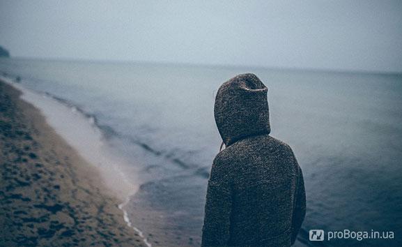 Самотня дівчина в пасмурний день на березі океану